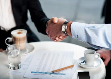 Business handshake over a coffee